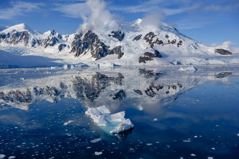 Antarctic landscape with snow covered mountains, glacier, dark blue sea with ice floes and reflections, Paradise Bay. Southern Ocean with small iceberg in front stock photo