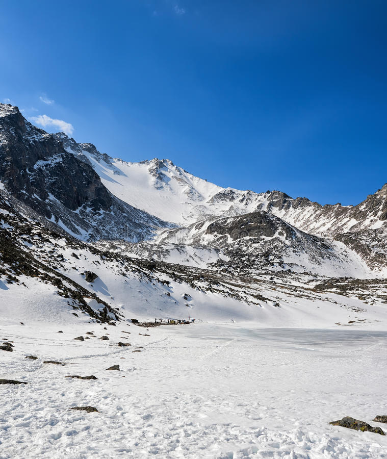 Southern slope of peak Munku-Sardyk. Assault camp on shore of frozen lake at foot of mountain. East Sayans. Russia royalty free stock photography
