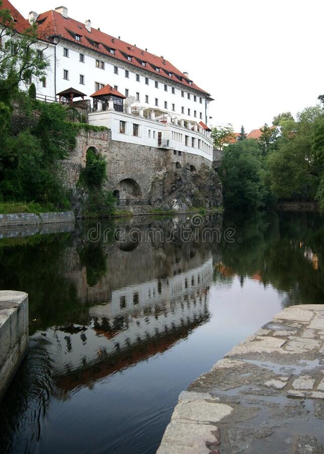 Southern wall of the former Jesuit Monastery reflecting in the Vltava River at dusk, Cesky Krumlov, Czechia. Southern wall of the former Jesuit Monastery stock images