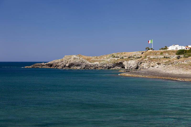 Southest Italian coast in Puglia region. An Italian flag on top of the cliff sings the border. Water has beautiful colors. In summertime stock image