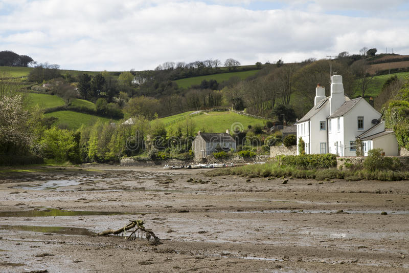 Southpool creek with houses and hilly fields in Devon. With mud banks at low tide royalty free stock photo