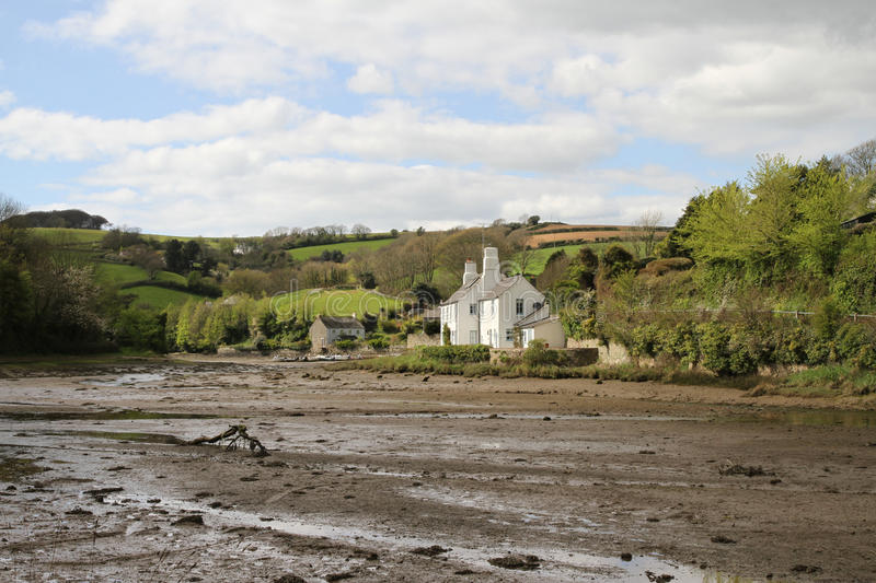 Southpool creek with houses and hilly fields in Devon. With mud banks at low tide. A wide view of Southpool creek Devon royalty free stock image