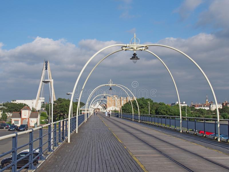 The historic pier in southport merseyside with people walking towards the town and the suspension bridge and buildings visible beh. Southport, merseyside, united royalty free stock images
