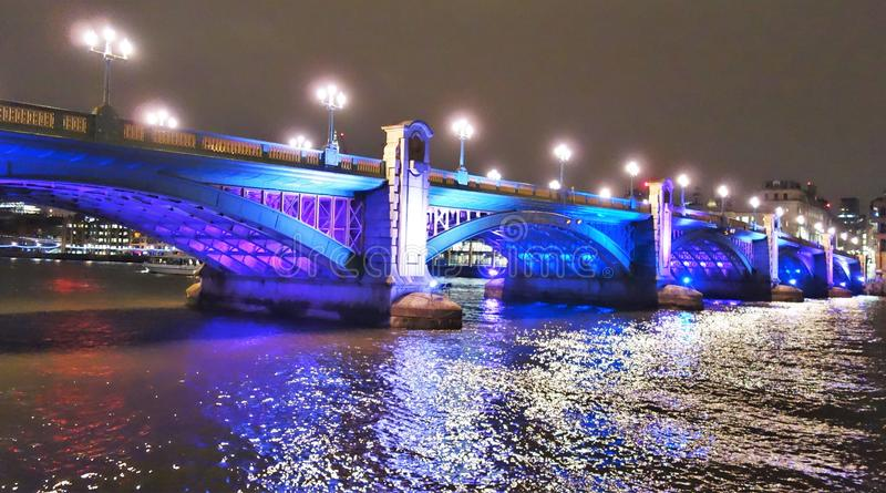 Southwark Bridge. At night in blue color along the River Thames in London, England stock photo