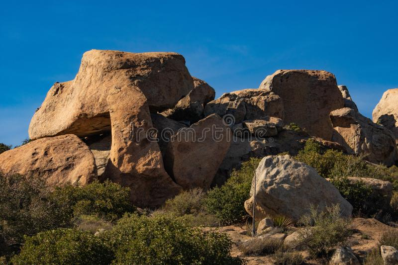 Southwest desert landscape, blue sky, desert plants, yucca and large boulders in foreground,. Southwest desert landscape-blue sky, desert plants, yucca and stock images