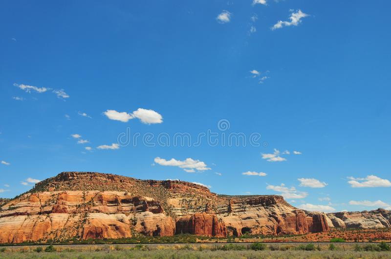 Southwest Landscape with Train. Traveling across country with blue sky with clouds and telephone wires crossing the landscape royalty free stock image
