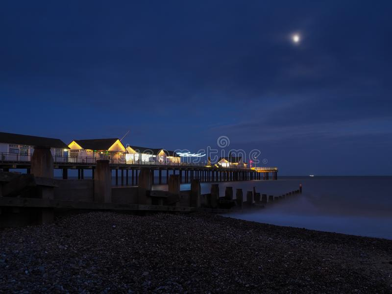 Southwold Pier brandde 's nachts op bij een houten grond onder een heldere maan met een schip aan de horizon, Suffolk royalty-vrije stock foto