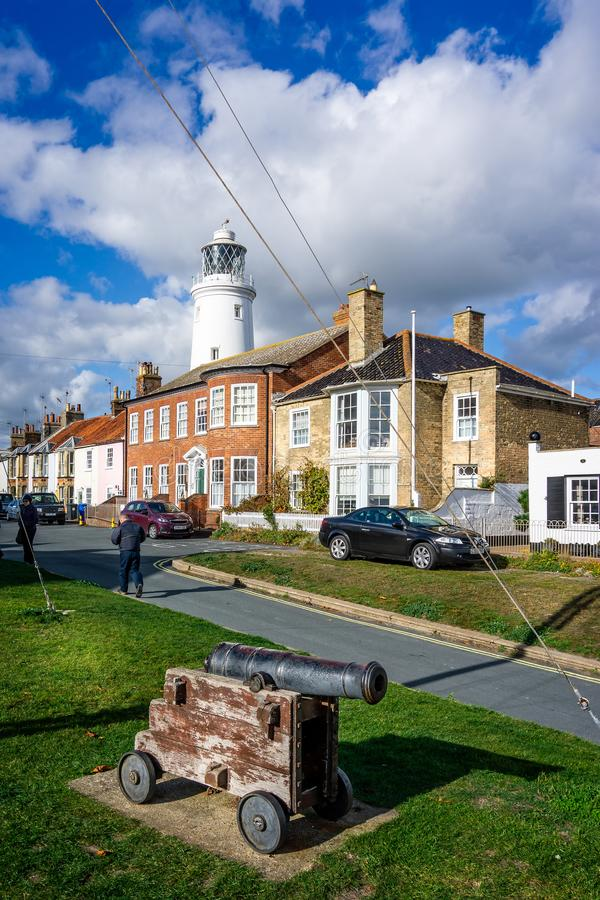 Southwold`s iconic lighthouse seen behind houses with cannon in foreground in Southwold, Suffolk, UK royalty free stock photos