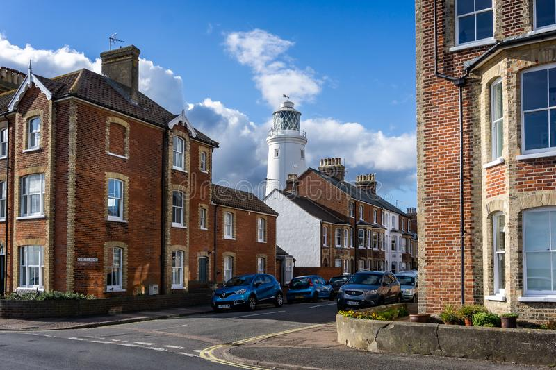 Southwold`s iconic lighthouse seen behind houses in Southwold, Suffolk, UK stock photos