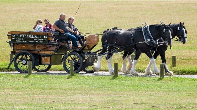 SOUTHWOLD, SUFFOLK/UK - 30 DE JULHO: Povos que apreciam um cavalo e um Ca imagem de stock royalty free