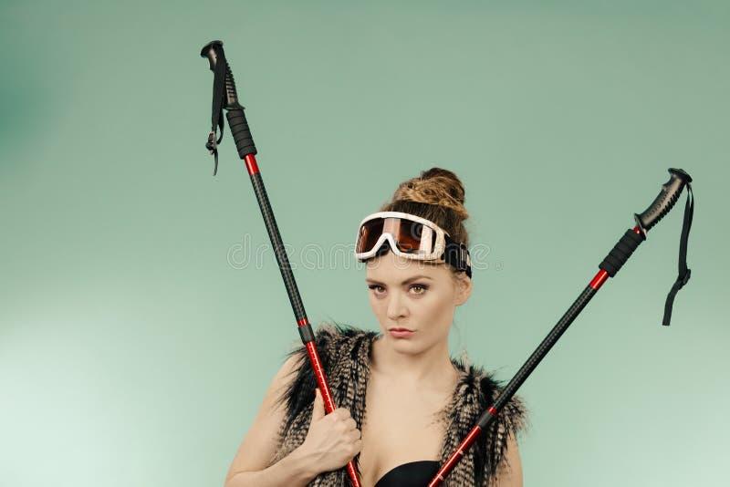 Soutien-gorge de port de femme et tenir des poteaux de ski images libres de droits