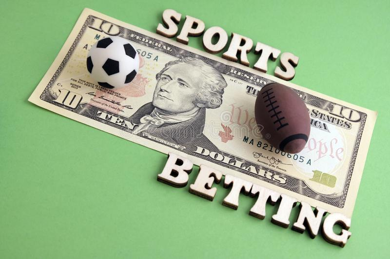 Souvenir balls for a game of soccer and rugby or football are on the bill of ten dollars. The concept of sports betting. The stock photos