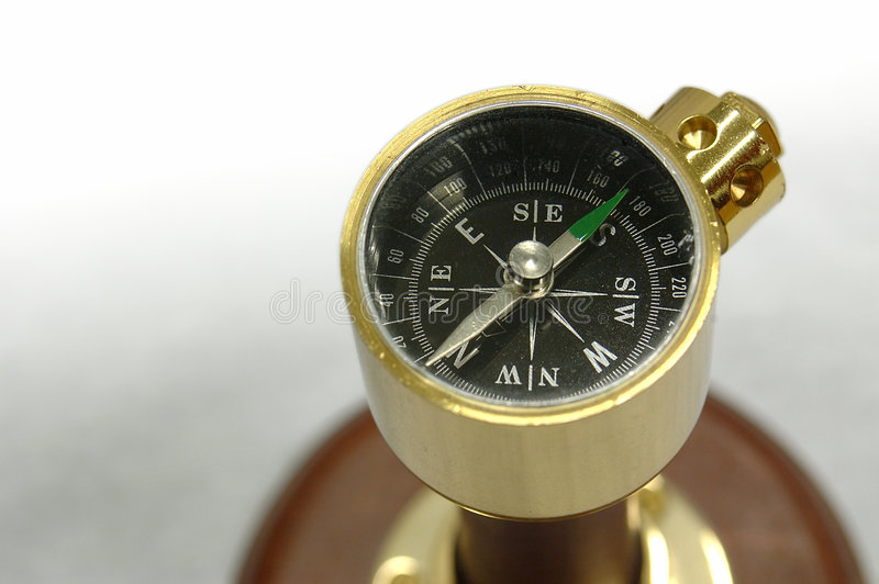 Souvenir Compass. Closeup of a brass souvenir compass on stand. The front edge is slightly out of the depth of field. Clipping path stock photo