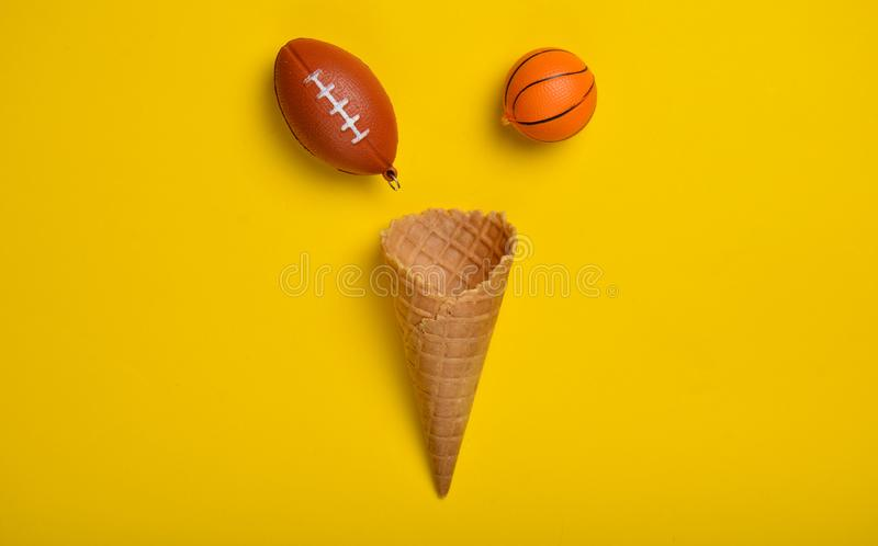 Souvenir keychains of rugby, basketball and waffle horn on a yellow background. Creative layout, sports concept, top view, minimal royalty free stock images