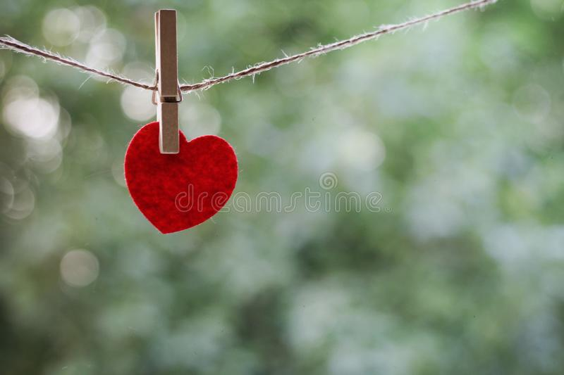 A souvenir in the shape of a heart red color hanging on the clothespin on blurred green background closeup/ the. A souvenir in the shape of a heart froom the red stock photography