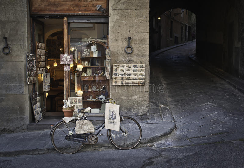 Souvenir shop, bike and Florentine street. Souvenir shop in Florence,Italy with a retro bicycle in the front with some souvenir on it ... beside the shop is one stock photos