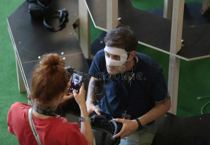 Souvenir at Vr devices testing in sonar Barcelona. A man gestures on a forest background while wearing virtual reality VR equipment during Sonar advanced stock image