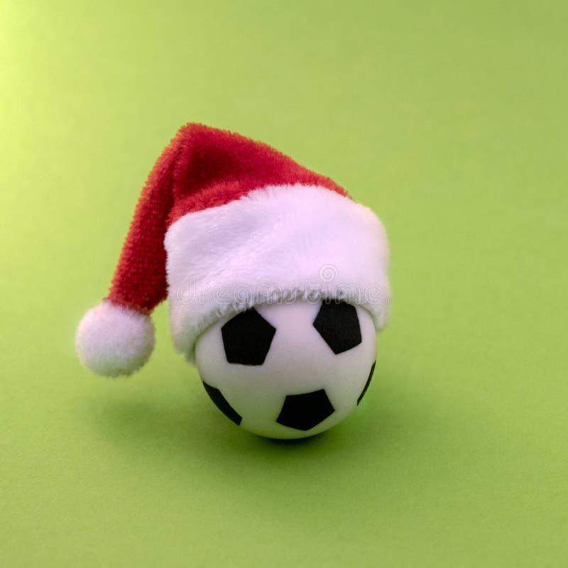 Souvenirfotbollboll i en röd Santa Claus hatt på en grön bakgrund kopiera avstånd Begreppet av sportjulgåvan Symbolet royaltyfri foto