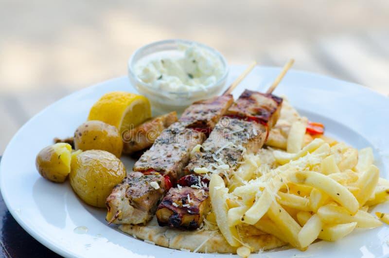 Souvlaki da galinha com batatas e o traditio fritados do molho do tzatziki imagem de stock