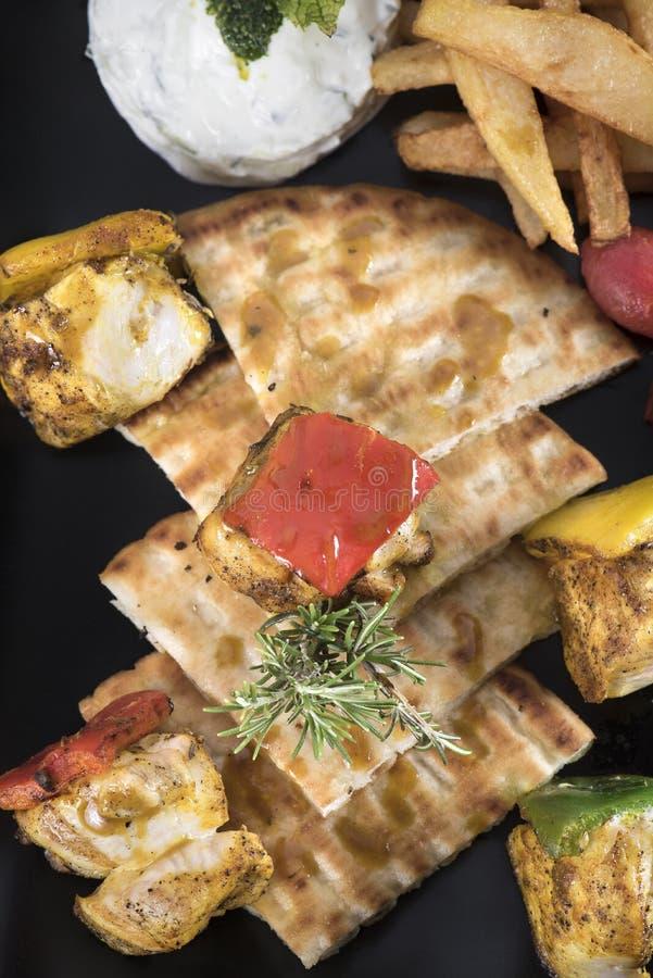 Souvlaki de poulet avec les pommes de terre, la sauce à tzatziki et le pain pita frits 7close vers le haut de vue au dessus du ti photographie stock libre de droits