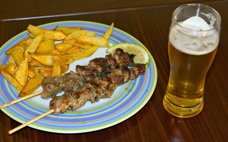 Souvlaki, fried potatoes and beer royalty free stock image