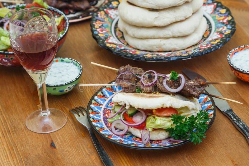 Souvlaki greco con il pane della pita e vegs freschi su una tavola fotografia stock libera da diritti