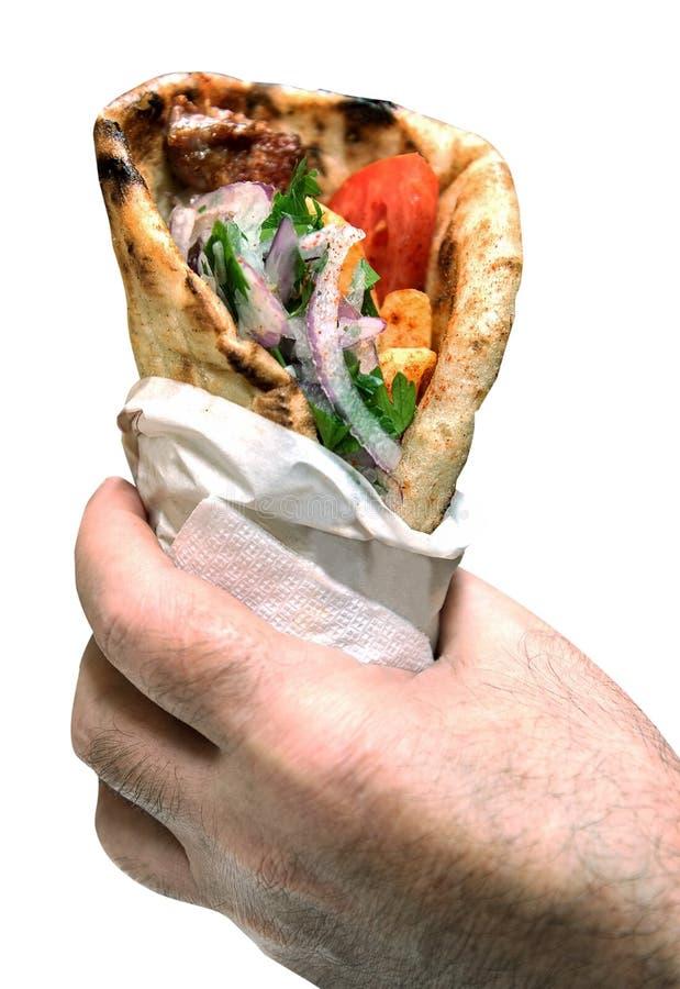 Souvlaki greco delle girobussole della pita nelle mani fotografia stock