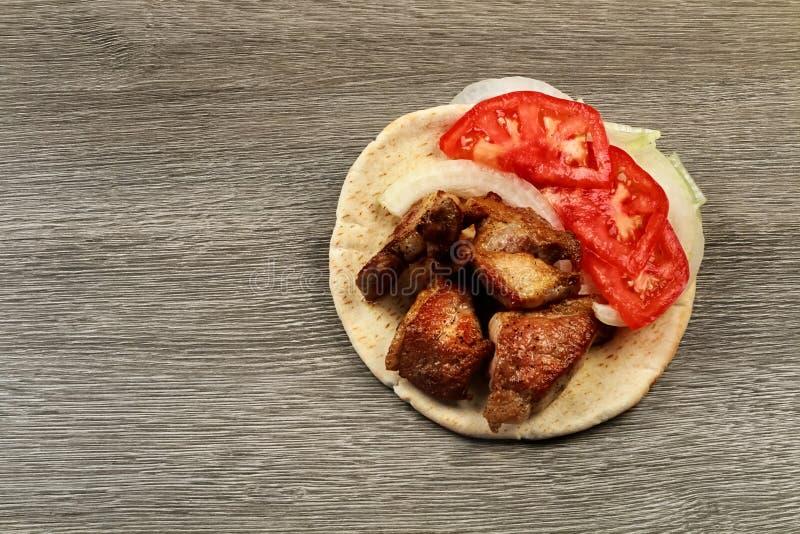 Souvlaki griego con el pan Pita y el primer de las verduras en la tabla Tabla del cerdo imágenes de archivo libres de regalías