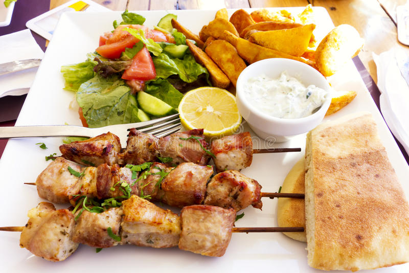 Souvlaki on white plate with salad, potatoes, bread and tzatziki sauce stock image