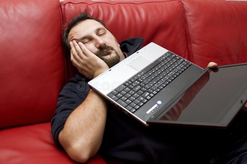 sova för holdingbärbar datorman royaltyfri foto