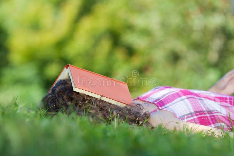 Sova flickan med boken på huvudet royaltyfri bild