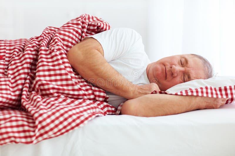 Sover den mogna mannen för stillhet i säng arkivbild