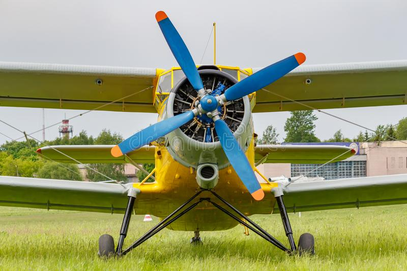 Soviet aircraft biplane Antonov AN-2 with blue four blade propeller and yellow fuselage parked on a green grass of airfield. Closeup royalty free stock image
