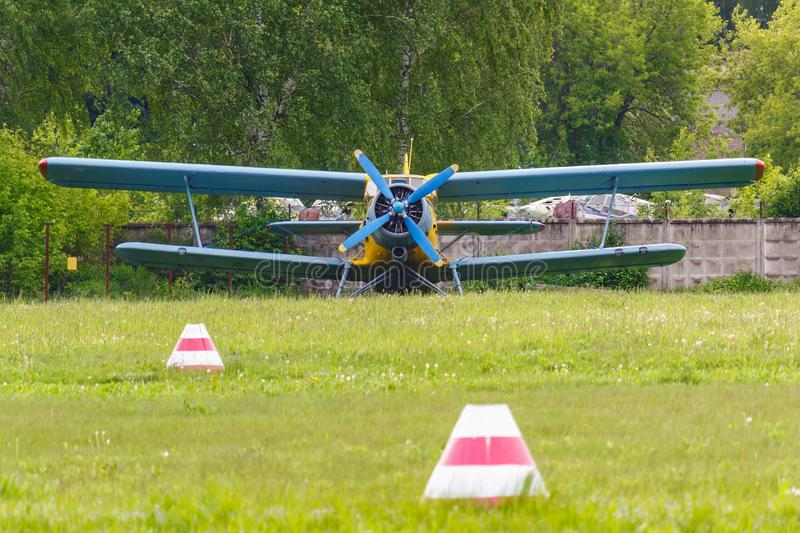 Soviet aircraft biplane Antonov AN-2 parked on a green grass of airfield stock photography