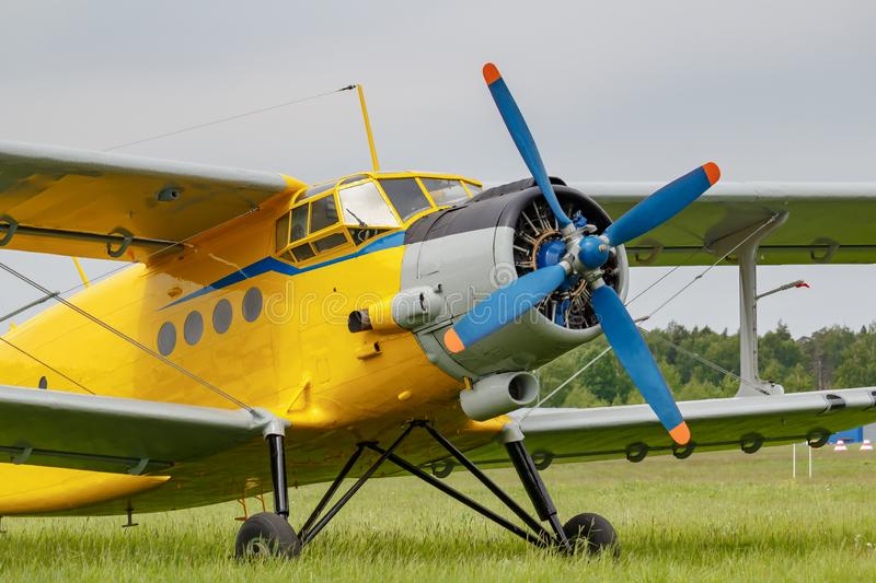 Soviet aircraft biplane Antonov AN-2 with yellow fuselage parked on a green grass of airfield closeup on a cloudy day royalty free stock images