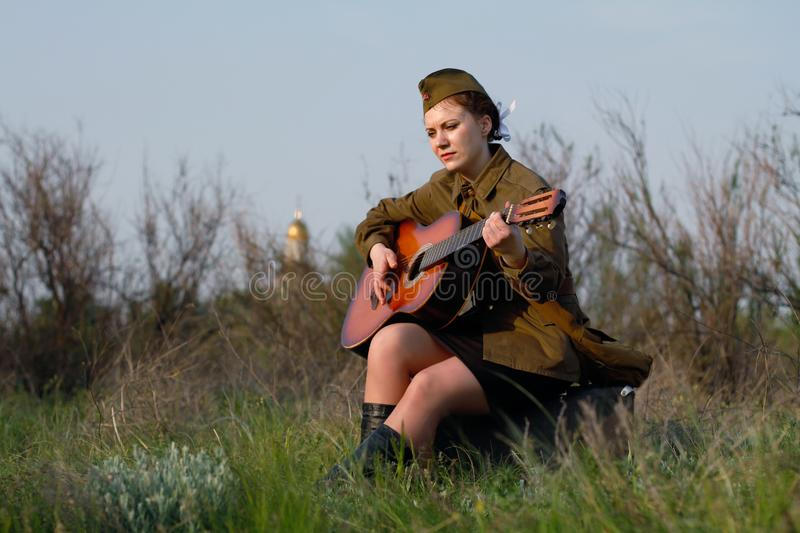 Soviet female soldier in uniform of World War II plays the guitar stock image