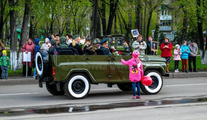 Soviet military suv, the girl gives the flower to the war veteran. People stand with photos and celebrate the victory parade in th stock photos