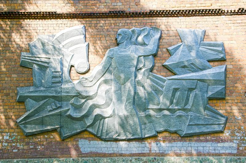 Soviet worker. Metal embossing on the wall on the wall of the old, Soviet stadium. Remained only in the photo. royalty free stock image