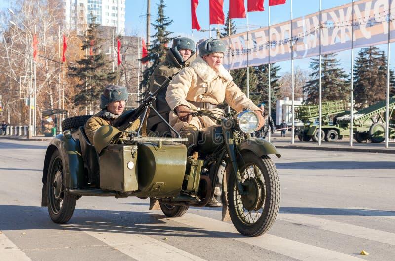 Sovjet tjäna som soldat med vapen på den gamla armémotorcykeln arkivbild