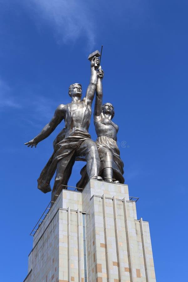 Sovjetisk monumentarbetare och kollektivjordbrukflicka på en bakgrund arkivbild