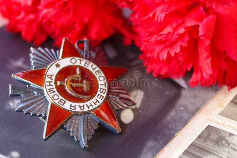 Sovjetorde van de Patriottische oorlog van de Patriottische oorlogsinschrijving met rode anjers tegen de achtergrond van oude fot royalty-vrije stock foto's