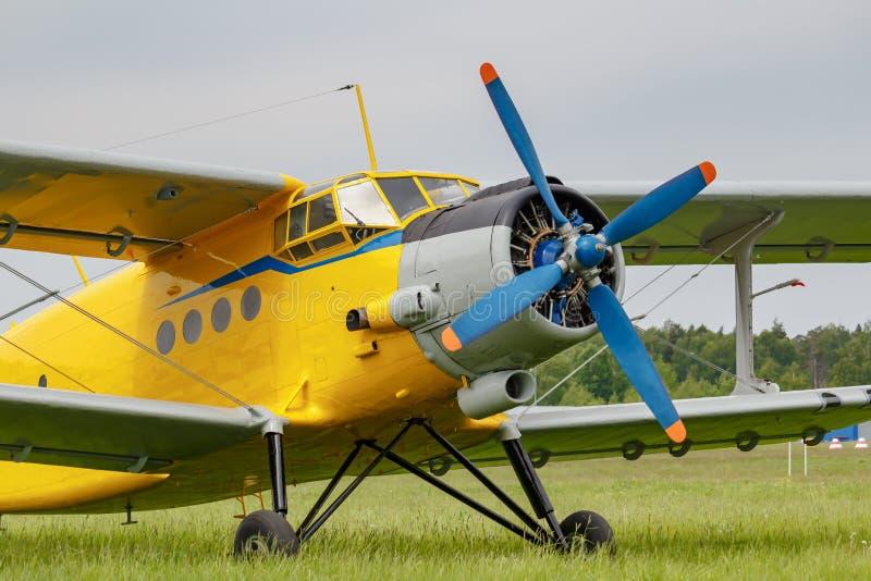 Sovjetvliegtuigentweedekker Antonov een-2 met gele die fuselage op een groen gras van vliegveldclose-up wordt geparkeerd op een b royalty-vrije stock afbeeldingen