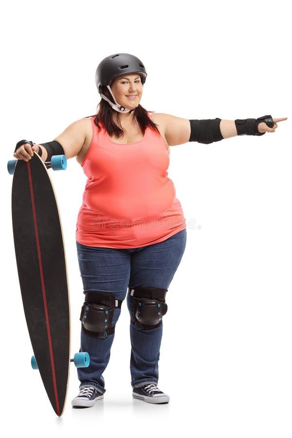 Sovrappeso con l'ingranaggio protettivo che tiene un longboard ed indicare immagine stock libera da diritti
