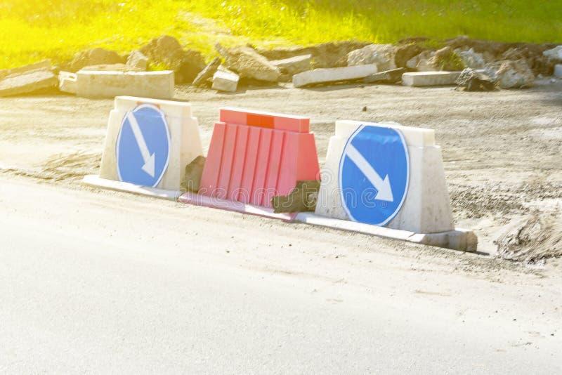 Sovrapposizioni delle bitte della strada e segnali stradali di plastica con le frecce su un fondo blu - deviazione alla destra immagini stock