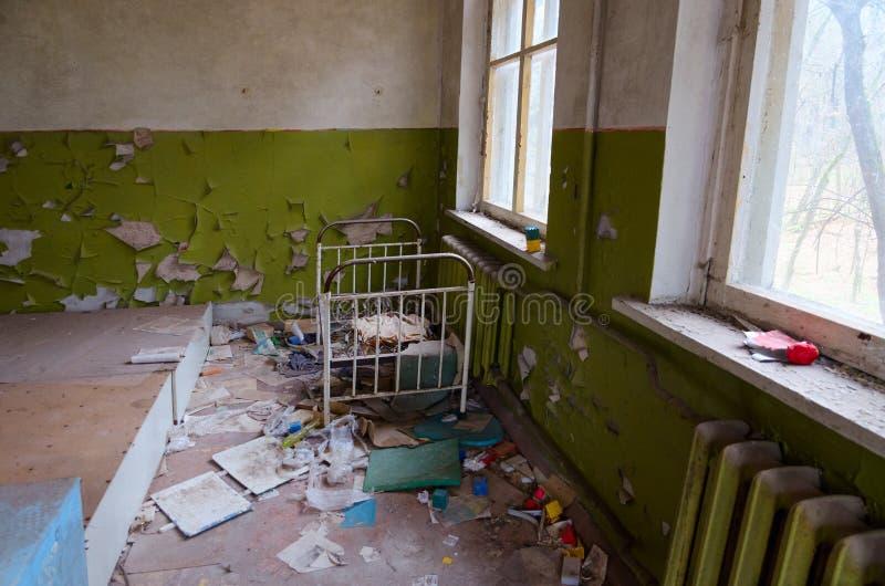 Sovrum i övergett dagis i förstörd zon för byKopachi uteslutande av den Tjernobyl kärnkraftverket, Ukraina royaltyfri fotografi
