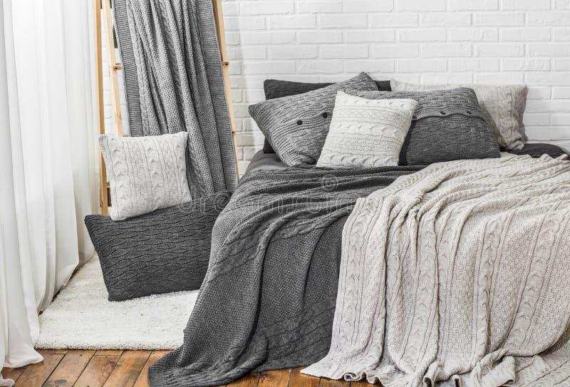 Sovrum i för plädkudde för grå vit signaler stucken säng royaltyfri foto