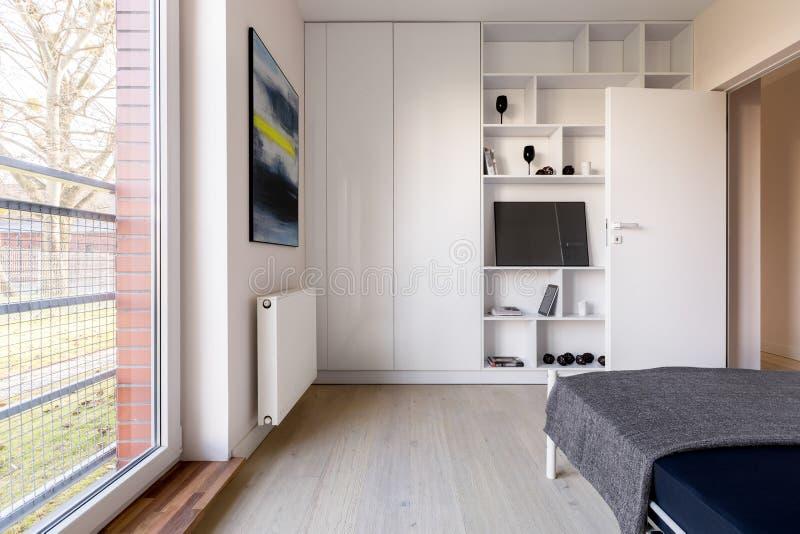 Sovrum med bokhyllan och garderoben royaltyfria foton