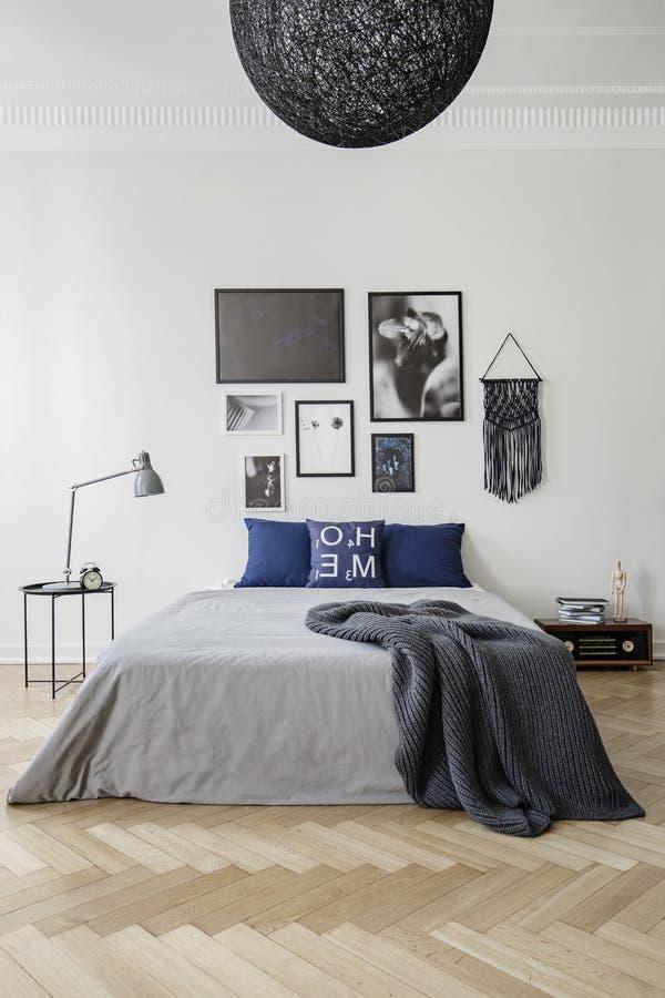 Sovrum med konungformatsäng med blåttkuddar, det gråa duntäcket och filten, galleri av inramat konstverk på väggen royaltyfri bild
