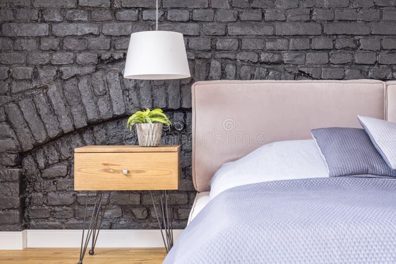 Sovrum med träsängkantkabinettet royaltyfria foton