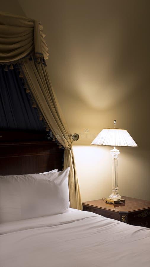 Sovrumhörn med gammalmodig säng med den viktorianska markisen och lampan med dunkelt ljus royaltyfri foto